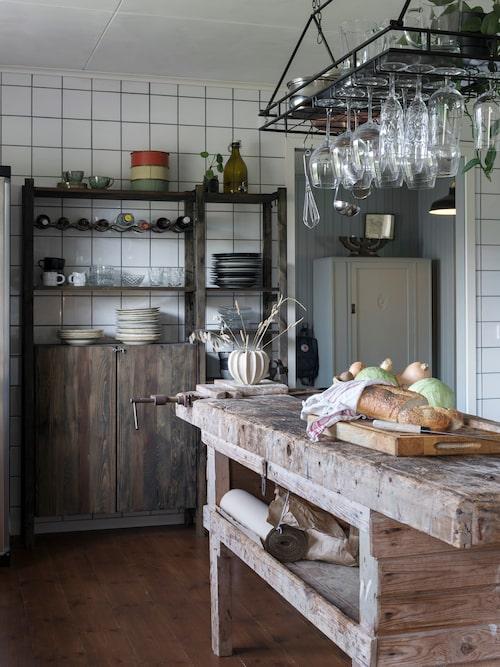 En gammal hyvelbänk från Petters pappa fungerar som köksö. Hängande hylla över snickarbänken, från Mio. Liten vas, från By on.