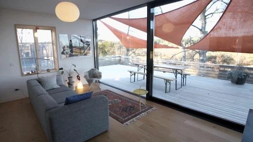 Baksidan har stora fönster som vetter mot terrassen.