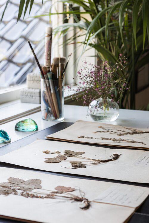På skrivbordet ligger vackra växtherbarium som Marias morfar Eric Sabel gjorde när han läste till agronom. Brevpressar med olika djurmotiv, House Doctor.