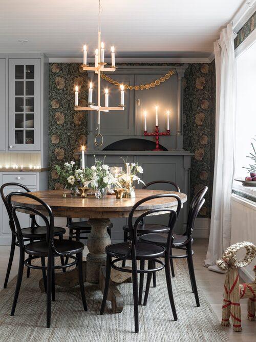 Tapeten från William Morris skapar stämning ihop med de gedigna möblerna. Kristofer har byggt ljuskronan. Bord, Mio. Stolar, Thonet.