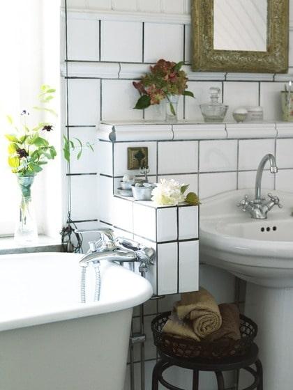 Smart lösning. Problemet med rören till badkarsblandaren löstes med hjälp av en liten inkaklad nisch som också  fungerar som avställningsplats bredvid handfatet.