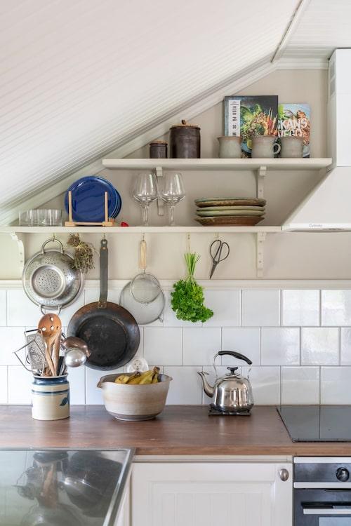 Öppna hyllor förstärker hemmets gammaldags karaktär. Kanna med köksredskap, loppisfynd.