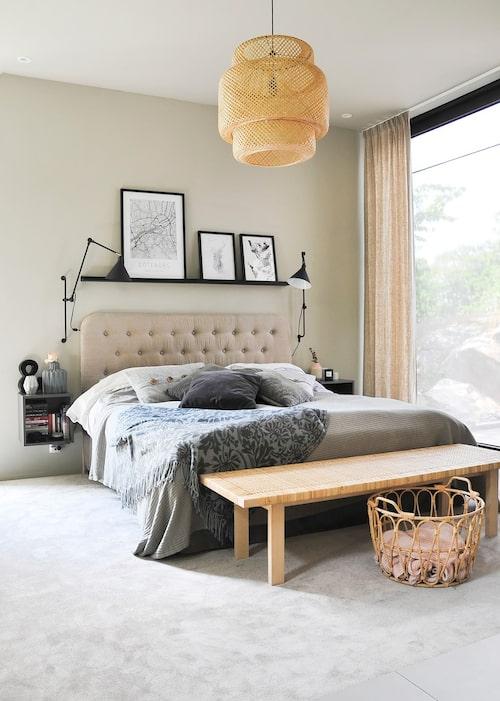 Emelie och Johans sovrum ligger på första våningen och har generöst fönster mot poolen och trädgården. Heltäckningsmattan runt sängen ramar in och skapar en mjuk känsla i rummet. Taklampa och bänken, Ikea. Gardiner och sänggavel, specialbeställda. Överkast och kuddar, Himla.
