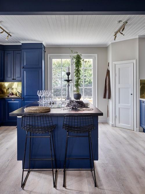 """Julia och Jim har låtit sätta in dubbeldörrar i köket som leder ut till altanen. Paret har även låtit sprutmåla köksluckorna i blått och har satt en mässingsplåt över kaklet. """"Vi har gett vårt kök en snabbmakeover i väntan på att totalrenovera det. Vi ska ha en sex meter lång köksö med inbyggt matbord och mörka ekluckor. En bekant som är konstnär kommer att göra en vägg och takmålning i köket"""", säger Julia."""
