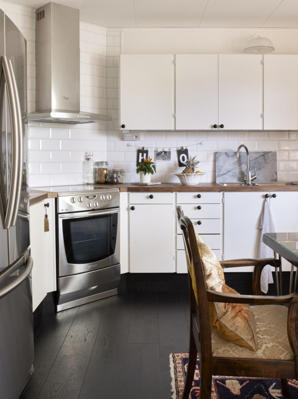 Piffat kök. Köket har piffats upp med nytt kakel och mörkt golv som får det vita standardköket att se exklusivt ut.