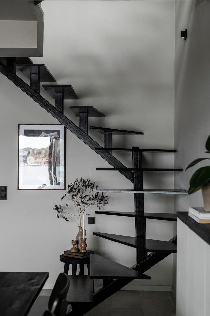 Den egendesignade svarta trappan löper smidigt längs ena väggen och förbinder de tre våningsplanen.