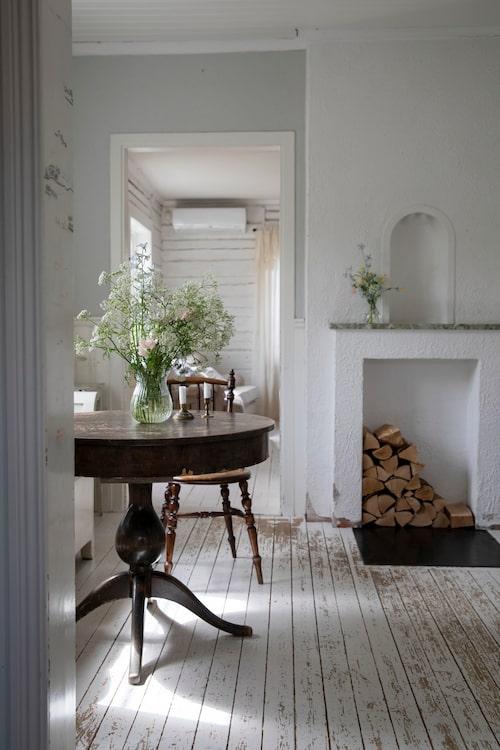 Helena fyller gärna huset med blommor. Köksstolen och glasvasen på bordet är loppisfynd. Matbordet är en gåva från Helenas mormors moster.