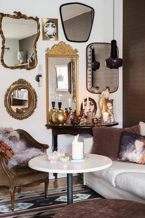 """""""Jag har en passion för speglar. De gör rummet större och jag kan ligga länge på soffan och titta på allt som speglar sig och bara filosofera"""", säger Malin. Operasopranen Lina Cavalieris ögon kikar tillbaka från de inramade tapetbitarna, designade av den italienske formgivaren Piero Fornasetti."""