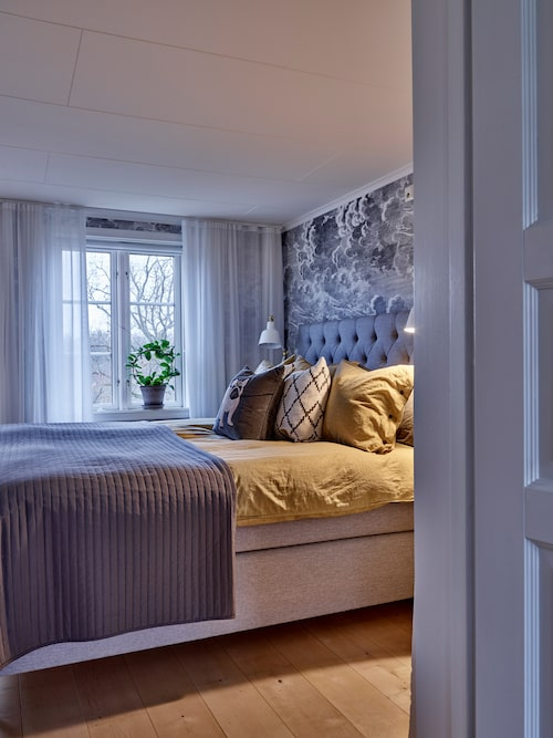 """""""Sovrummet är ganska litet så här inne har vi bara vår säng. Vi gillar att vi har tillgång till balkongen härifrån. Det är underbart att ta med sitt morgonkaffe ut på sommaren."""" Säng, Mio. Kuddar från Jotex och Tyghuset Taberg."""