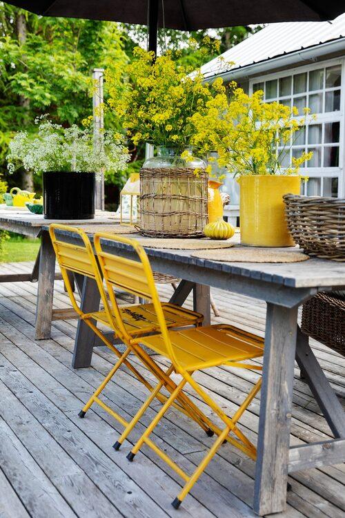 Gula stolar och raps i stora vaser lyser upp terrassen mellan huset och poolen. Stolar, Oscar & Clothilde.