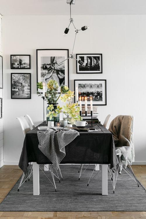 Matplatsen i vardagsrummet är den som används mest. Den grå mattan ramar in och markerar liksom de svartvita fotografierna i enhetliga ramar. Matta, bord och ramar, Ikea. Taklampa Jotex. Stolar, Ilva. Ljusstake Cubus från By Lassen. Vas H&M Home.