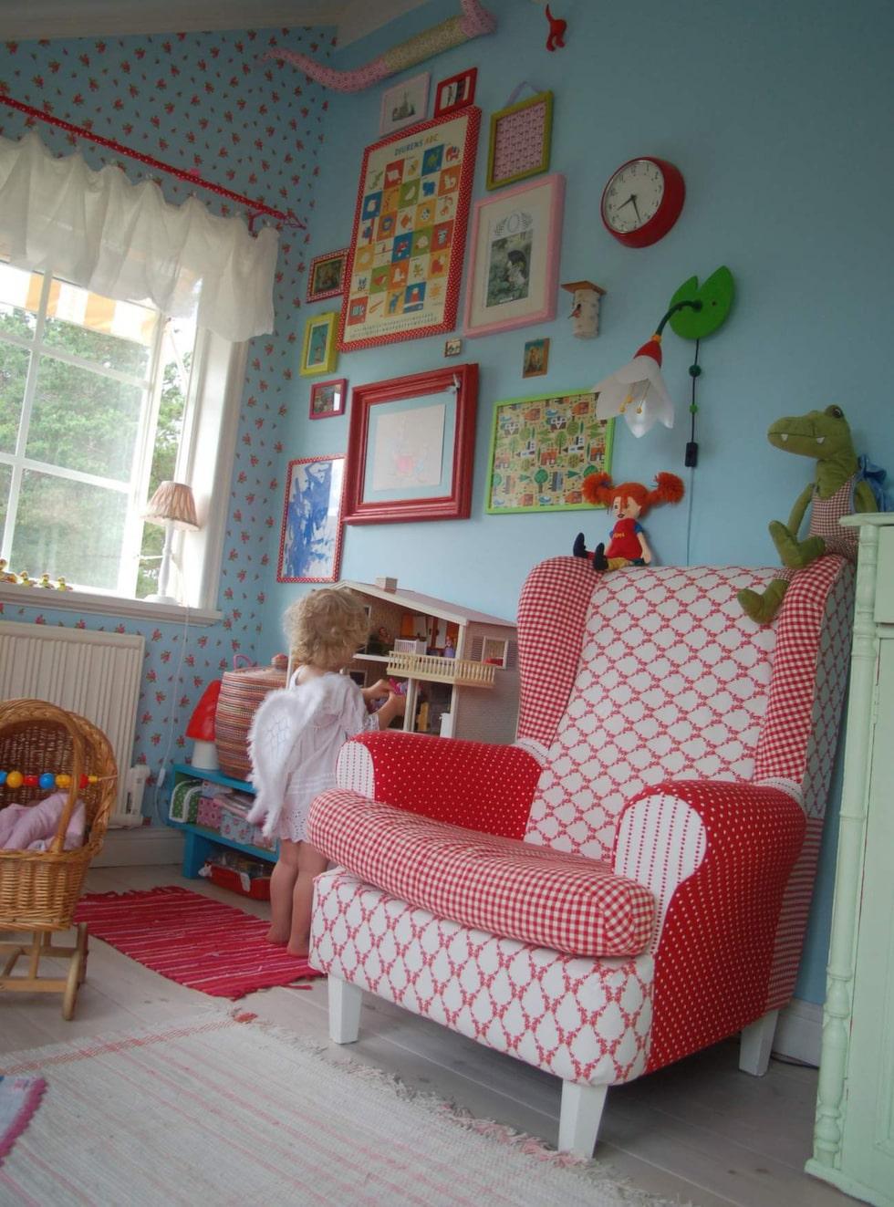 Den turkosa väggen kompletteras med en lika turkos tapet på en annan vägg, men med motiv av vita små prickar och rosa rosor.