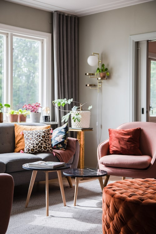 Vardagsrummets grå soffa har följt med i många år. Intill står fåtölj och puff från Sofa company i Huskvarna. Blomsterpiedestal från Sofias morföräldrar.