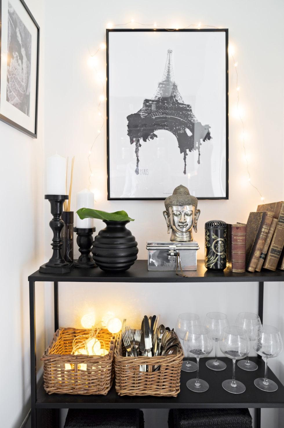 Den svarta plåthyllan från Villa tretton fungerar som extra avställningsyta i köket och rymmer även bestick och glas. Posters på väggen från Desenio.