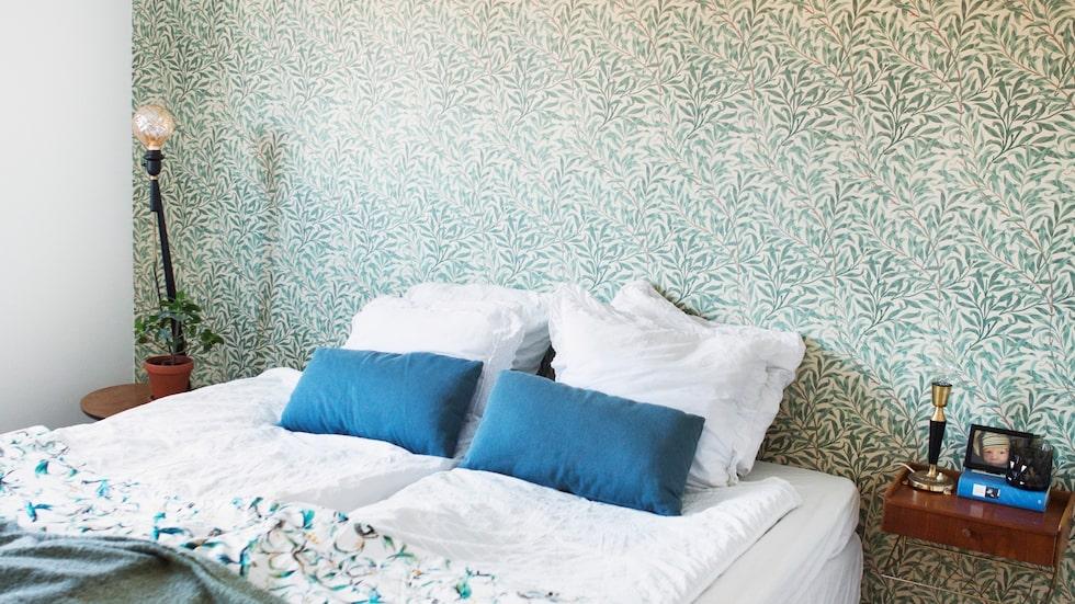 Golvet i sovrummet på bottenvåningen slipades och väggarna tapetserades med William Morris- tapeten Willow. Det blommiga överkastet kommer från H&M home.
