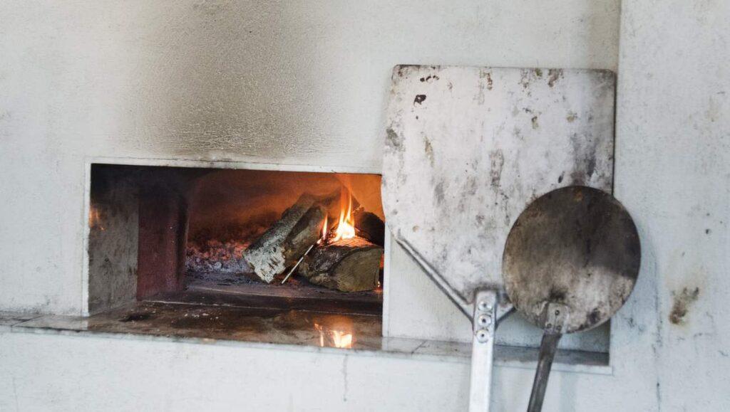 """I stenugnen som eldas med ek bakar Paolo neapolitansk pizza. """"Den smakar helt annorlunda från annan pizza, den blir liksom krispig"""", säger han."""