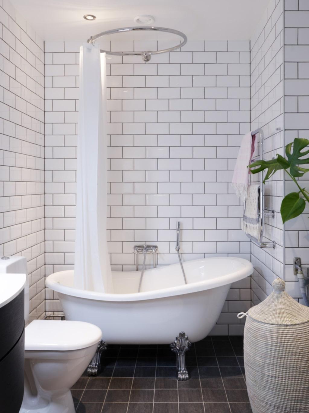 Svart fog. Badrummet har vitt kakel med svart fog och ett badkar med lejontassar.