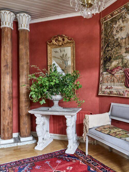 """Karl Fredrik och Petter har anlitat Maria Attström för att måla väggarna i hallen. """"Jag föll för engelskt rött som ger en exklusiv och välkomnande känsla tillsammans med guldspegeln, och det antika möblemanget vi valt"""", säger Karl Fredrik."""