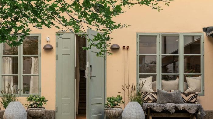 Här kliver man rakt ut till den grönskande innergården och flera uteplatser.
