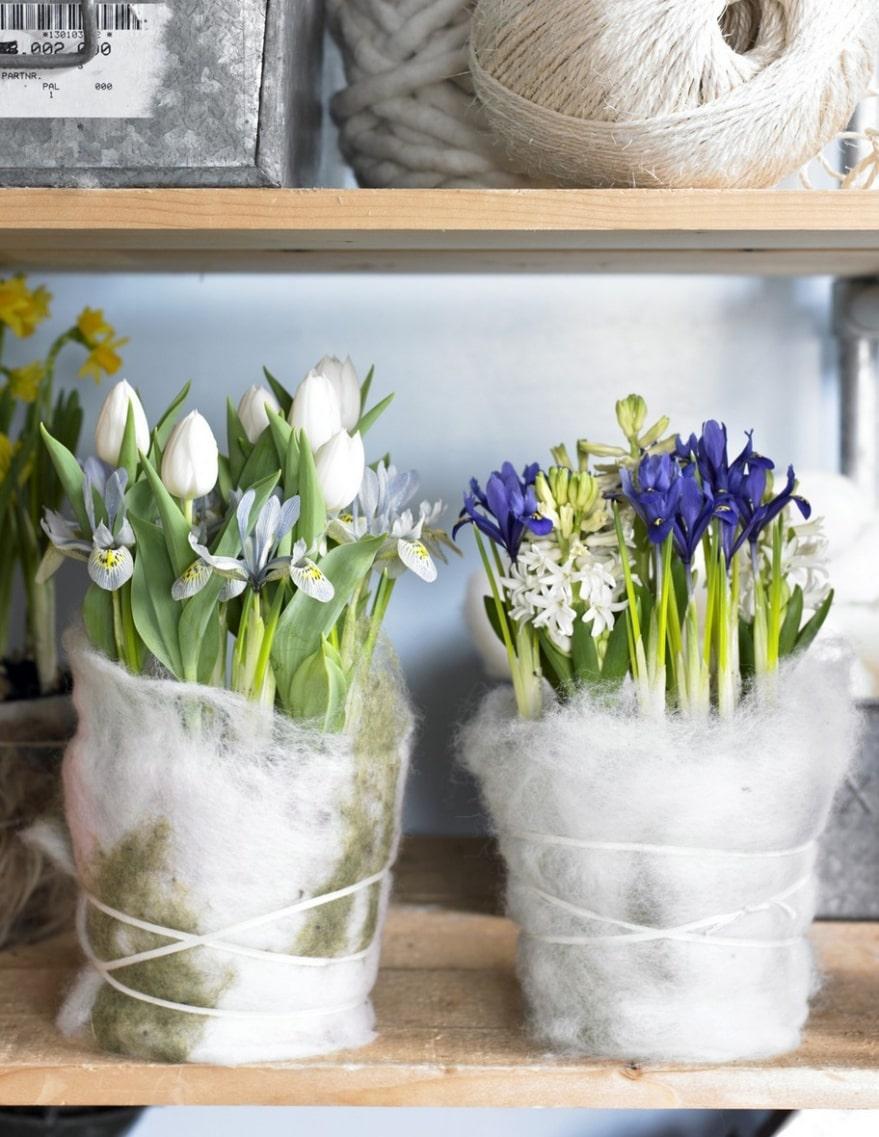 Trångt. Vira sisal eller något tovat tyg eller filt runt krukorna och knyt om med ett band. Svårare behöver det inte vara. Våriris, vita tulpaner och hyacinter står tätt tillsammans i krukorna.