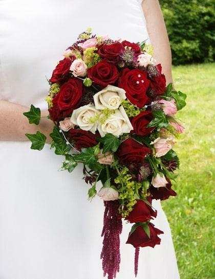 BLOMSTERPRAKT. Klassik bukett av röda, vita och rosa rosor bundna i en droppform tillsammans med murgröna.