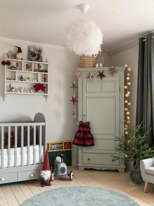 Lilla Hilmas rum är en riktig dröm med både gammaldags möbler och plats för lek och bus. En egen liten gran ger fin julstämning i rummet. Matta och säng, Ikea. Skåpet är ett second hand-fynd. Stjärngirlang, Indiska.