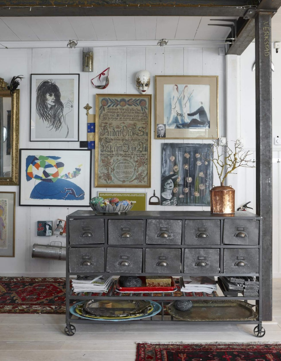 Efter ombyggnaden samlade Karin och René allt som satt på väggarna på en vägg. Byrån i metall är nytillverkad i gammal stil och matchar järnbalkarna perfekt.