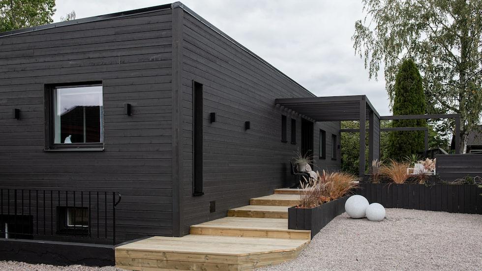 Huset som ursprungligen hade en fasad av rött tegel har fått en liggande träpanel målad i en helmatt svart kulör. Fasadfärg, från Demidekk.