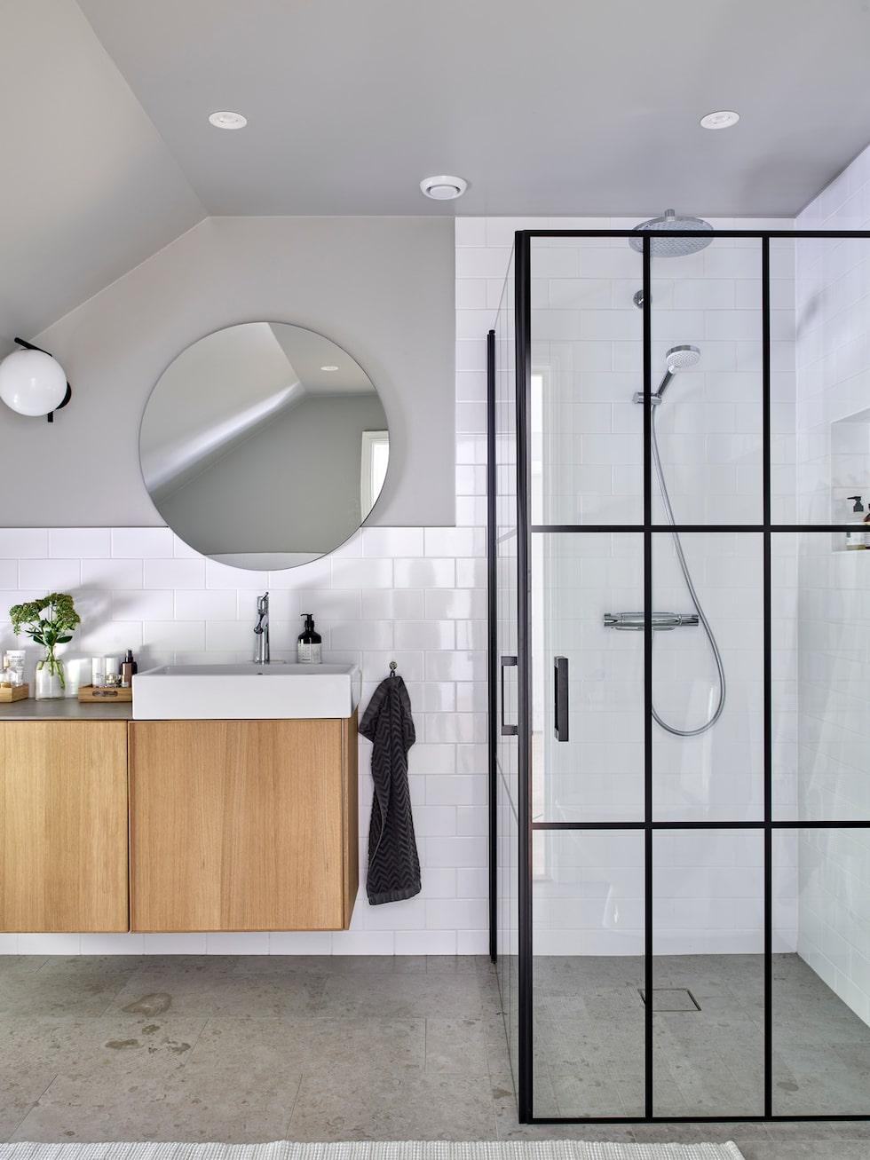 Badrummet på övre plan har fått en duschvägg i industristil. Kommoden är ett köksskåp från Ikea som byggts om till badrumskommod. Duschvägg, Duschbyggarna. Lampa IC Lights, Flos. Golv och även toppskiva på kommoden, granitkeramik Norrvange, Bricmate.