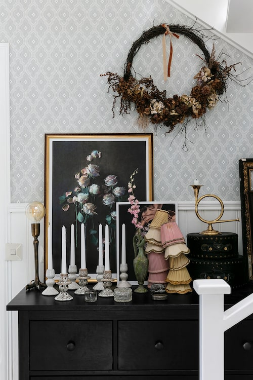 Ett stilleben med Lindas samling av gamla lampskärmar från takkronor. På väggen hänger en torkad krans som Linda gjort. Tapet, Viola, Sandberg. Ljusstakar i keramik, House Doctor.