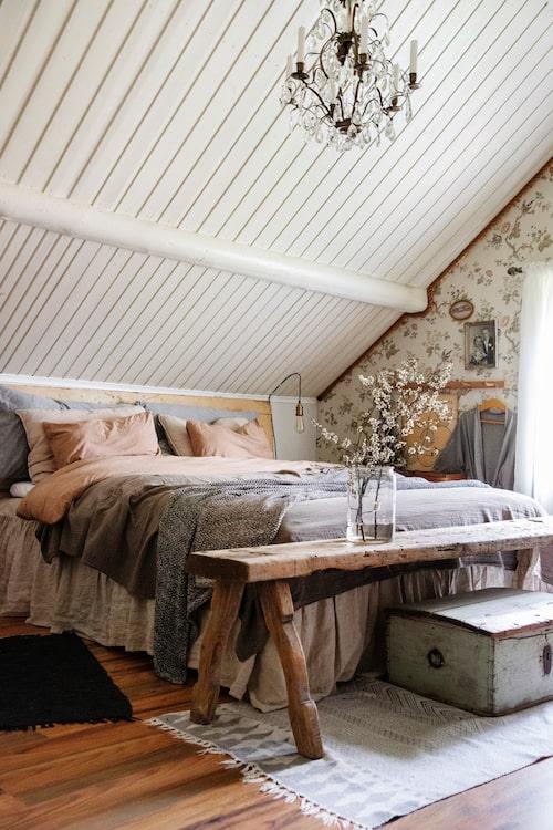 Under snedtaket på övervåningen har Linnea och Joakim sitt sovrum. Lakan, Navy Stories och Granit. Tapet ur Falsterbokollektionen, Boråstapeter. Matta, House Doctor. Kristallkrona och bänk, inköpta på auktion.