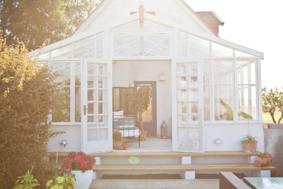 Rum av glas. Uterummet är byggt av gamla fönster och återvunna dörrar och glas. Uterummet är nu en förlängning av huset och köket.