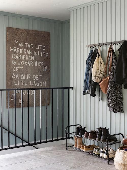 Hallens väggar har klätts in med pärlspont och ett klinkergolv lades in när Fanny och Petter tog över huset. Fanny har gjort skylten som nu hänger i trappan som dekoration på sitt och Petters bröllop.