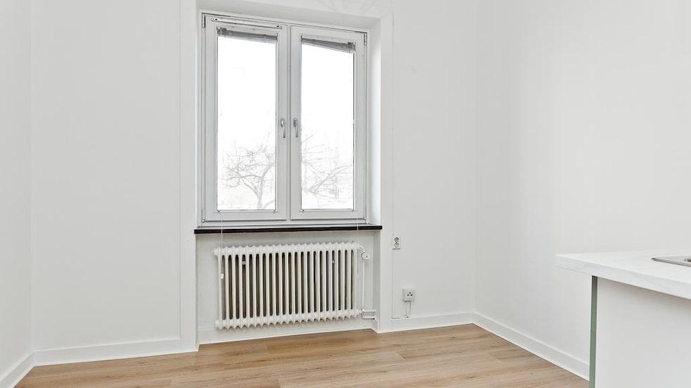 Ett rum med pentry. Vita väggar och parkettgolv.