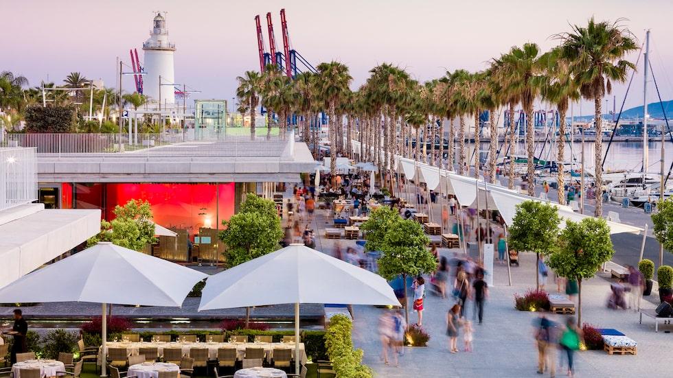 Kajen Muelle uno har förvandlats till restaurang- och shoppingstråk med Málagas välkända fyr i fonden