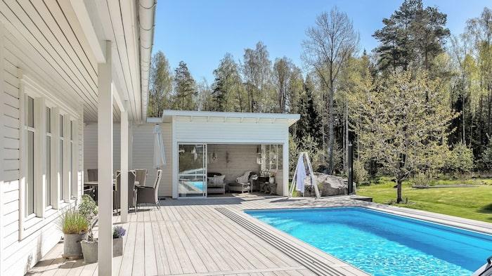 Stort altandäck i trä bredvid poolen och uterum med glasdörrar.