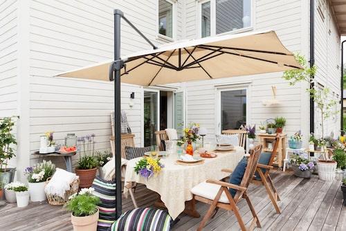 Den rymliga altanen har plats för många. Det stora parasollet ingick i husköpet och skuggar skönt varma dagar. Kuddar, Afroart. Duk, Chamois.