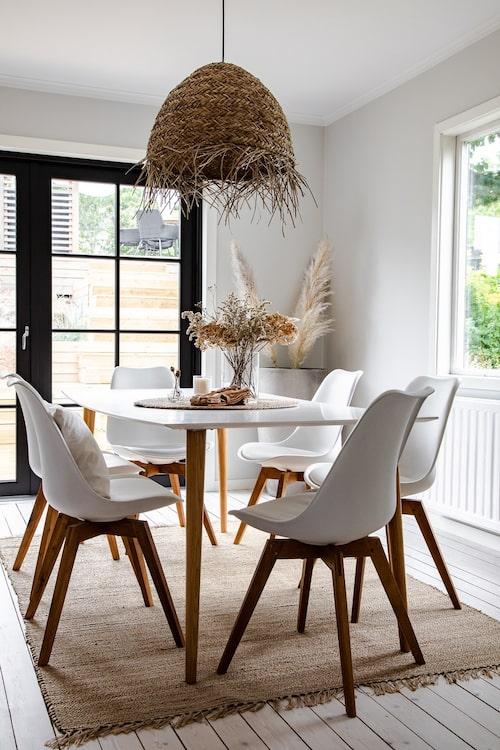 Från bordet i köket har man en fin utsikt över trädgården och de olika trädäcken, inne och ute suddas ut på ett skönt sätt. Bord och stolar, Mio. Lampa, Rusta. Matta, Zara Home.