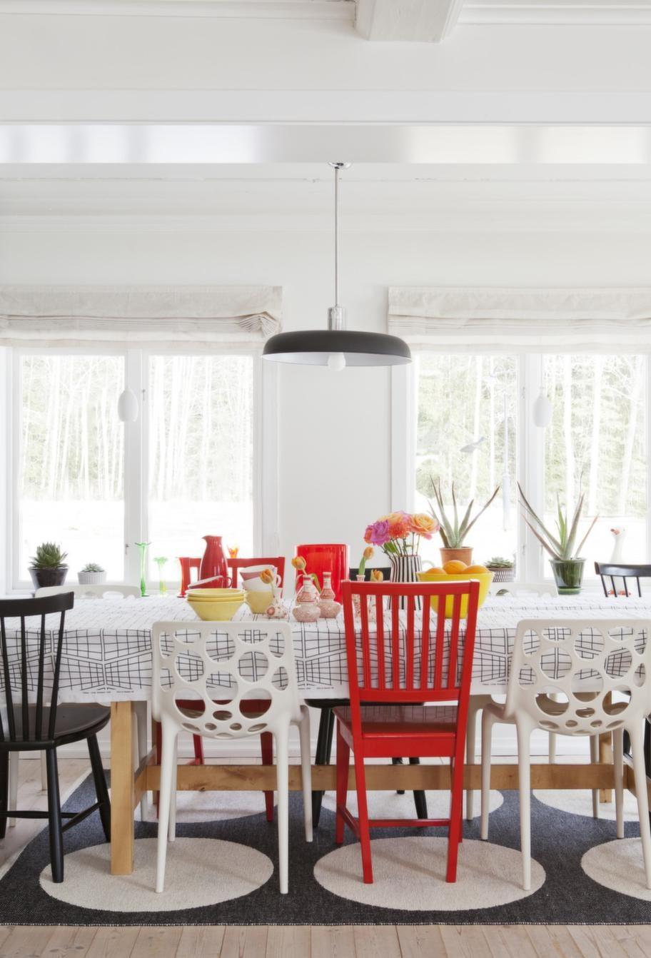 Stolar i olika färger runt matbordet Norden från Ikea. Lampan kommer från Olsson & Jensen. Duken är sydd av metervara från Ikea.