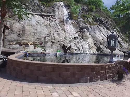 Till huset hör också en konstgjord sjö med vattenfall och en stor grillplats med eldstad.