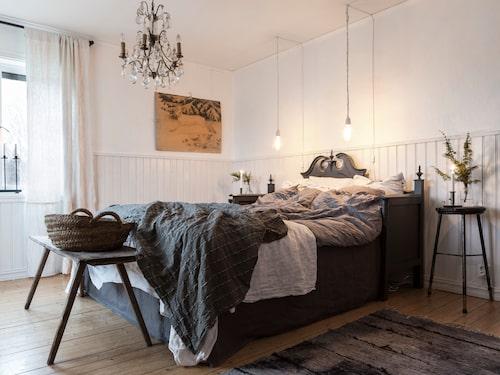 Sängen är en omgjord antik träsoffa med vackra sniderier, färgsatt i en mörkgrå linoljefärg. Två glödtrådslampor med lång sladd fungerar som sänglampor. Mattan är ett loppisfynd som Sandra har färgat om.