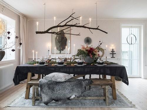 Matsalsbordet är dekorerat i naturens tecken. En gedigen gren har fått ny funktion som ljuskrona. Kristoffer har byggt bänken. Bord, Ikea. Matta, Mio.