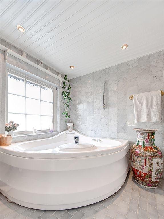 I anslutning till master bedrrom ligger ett stort badrum med en jacuzzi, Carrara marmorgolv, vitmålad furupanel i taket med spotlights, handfat med kommod, wc samt golvvärme.
