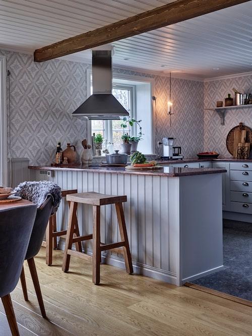 En praktisk köksö skiljer av köket från matrummet och är perfekt när frukosten eller buffén ska dukas upp. Barstol, Sika Design, Bredaryds Möbler. Ljuslykta, från Grafitgrå. Tapet, Ludvig Turquoise i kollektionen Arv, Sandberg.