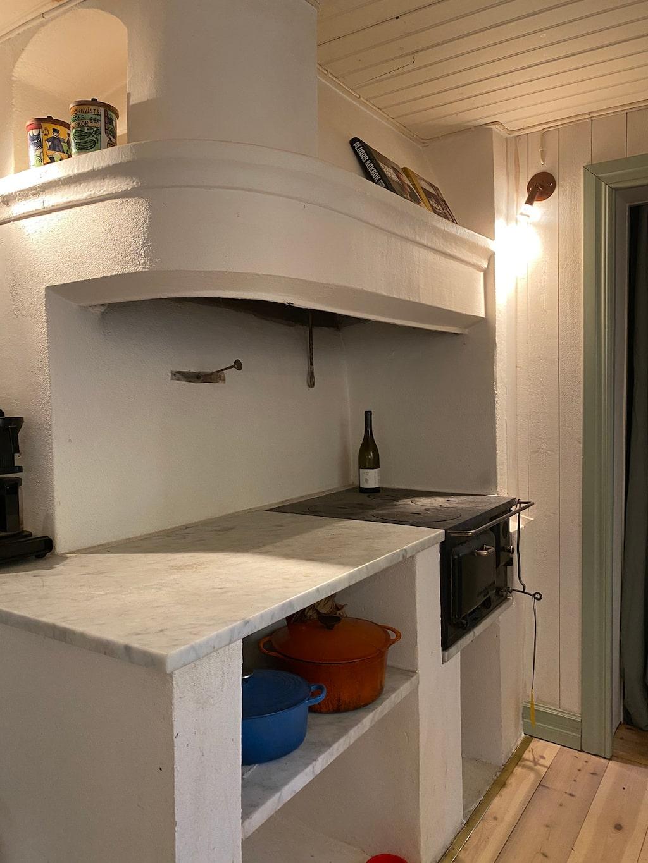 Den murade spisen i köket är troligtvis från 1700-talet. De vitmålade väggarna är ohyvlad plank och taket är pärlspont.