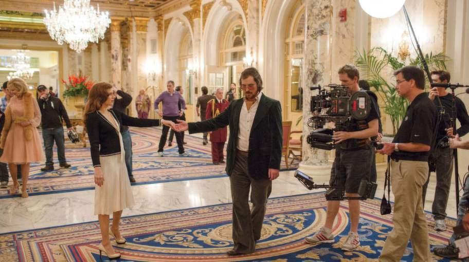 """""""American Hustle"""". Bedragaren Irving Rosenfeld (Christian Bale) och hans vapendragare Sydney Prosser (Amy Adams) möts en gång i den förgyllda lobbyn i Fairmont Copley Plaza i Boston."""
