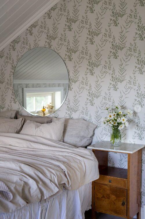 Sovrummets väggar är klädda med en vackert grönskande tapet. Sängborden är köpta på Blocket. Sängkläder, Åhléns. Sängkappa, Ellos. Spegel House Doctor. Tapet, Rusta.