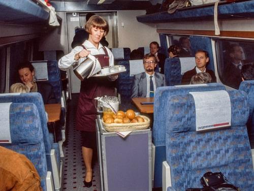 En tågvärdinna serverar kaffe till resenärer i första klass ombord på X2000. Året är 1990.