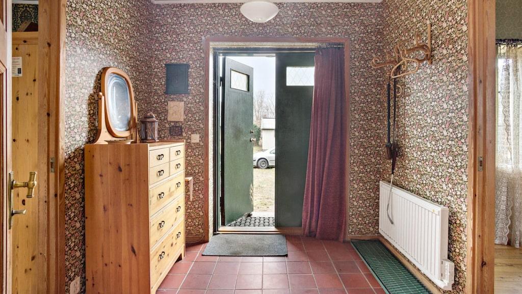 Hallen med blommiga tapeter, furubyrå, murrigt grön dörr och brunrött draperi.