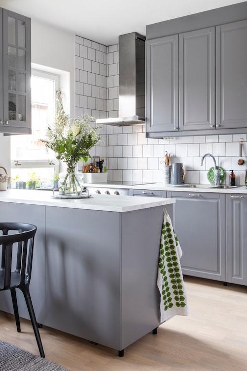 Där köksön står var det tidigare en betongvägg, som skilde köket från matrummet. I dag är det öppna rummet mer socialt och för att inte tala om ljusare! Matta, Jysk. Svart stol, Ikea.